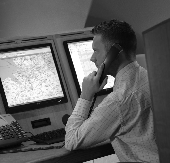 black and white photo of an Incident Manager on the phone whilst viewing a map on his computer screen