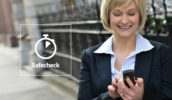 Woman on a street looking at an Alertcom T4 Device overlayed with our Safecheck icon